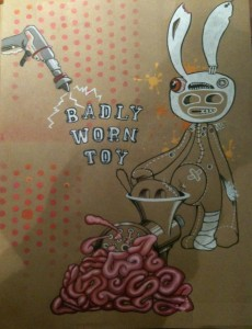 Poster for Badly Worn Toy showing a rather disturbing comic book rabbit putting itself through a mincing machine. Frankly you are lucky if you can't see it.